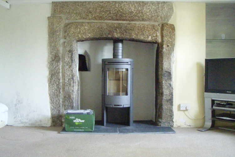 Contura 556 in traditional stone fireplace