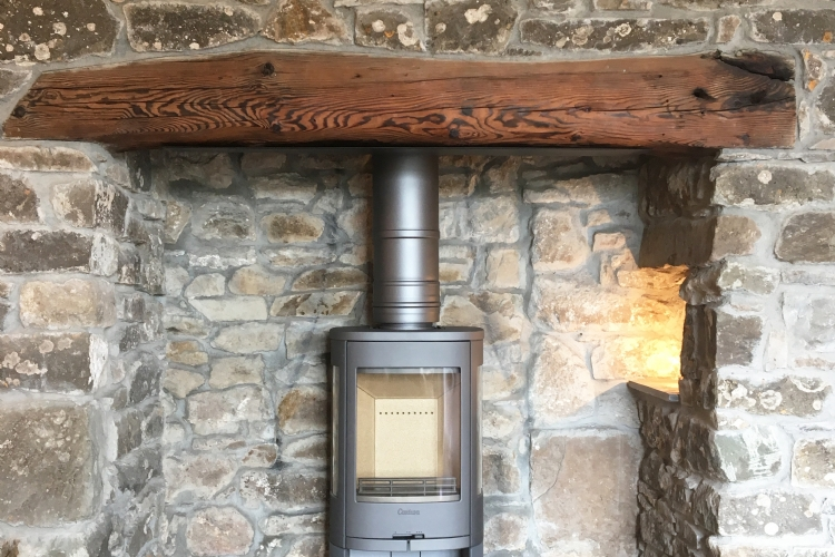 Contura 810 in a traditional stone fireplace